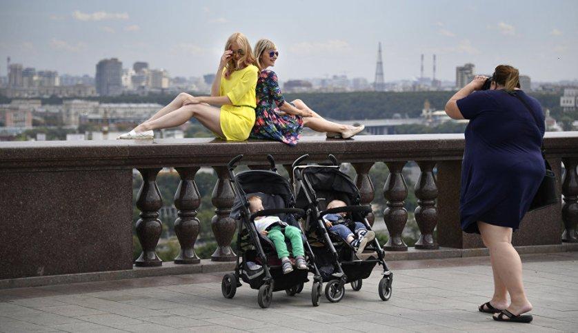 Девушки фотографируются на смотровой площадке на Воробьевых горах в Москве.