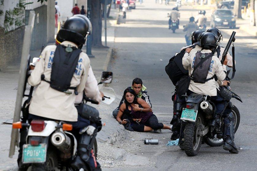 Пострадавшие от слезоточивого газа сторонники оппозиции во время митинга против правительства президента Венесуэлы Николаса Мадуро в Каракасе.