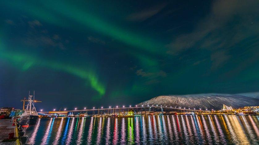 """Работа фотографа Derek Burdeny """"Прекрасный Тромсё"""" (Beautiful Tromso). На снимке - северное сияние в небе над гаванью норвежского города Тромсё."""