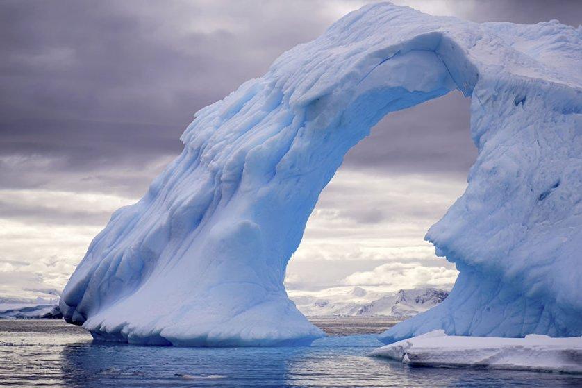 """Снимок """"Ледяные ворота"""" фотографа Гуды Чалун. На кадре - айсберг, плывущий в море у берегов Антарктиды. Эта арка сформировалась из-за воздействия ветра и температурных изменений, разрушивших лед."""