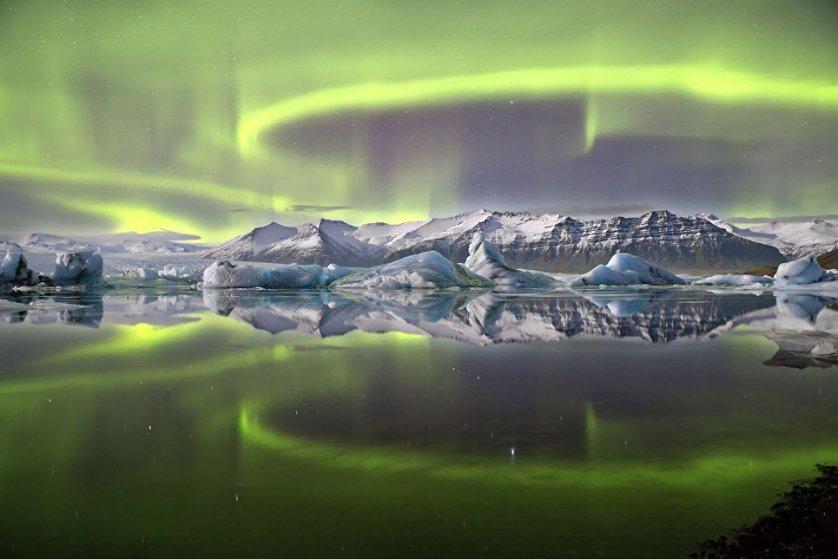 """Снимок """"Северное сияние над ледниковой лагуной"""" Джеймса Вуденда. Фото было сделано на озере Йекюльсаурлоун, расположенном на юге огромного ледника Ватнайекюдль в Исландии."""