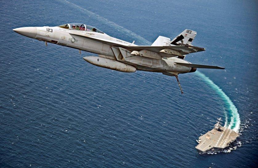 """Американский палубный истребитель-бомбардировщик и штурмовик """"Супер Хорнет"""" пролетает над авианосцем USS Gerald R. Ford в Атлантическом океане."""