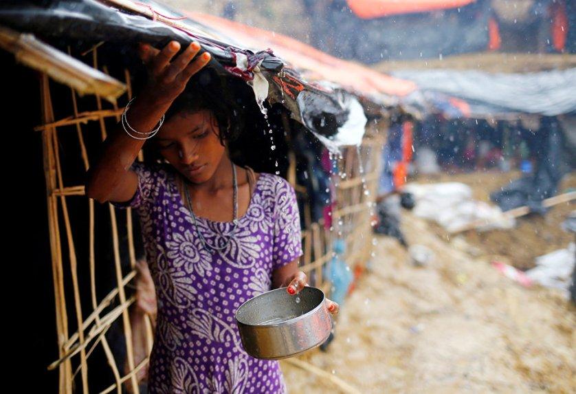 Девочка из народности рохинджа собирает дождевую воду в лагере для беженцев в городе Кокс-Базар, Бангладеш.