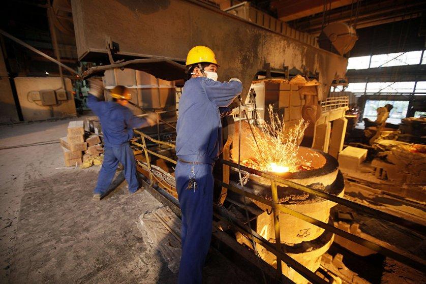 Работники на сталелитейном заводе в деревне Хуаси в провинции Цзянсу в Китае