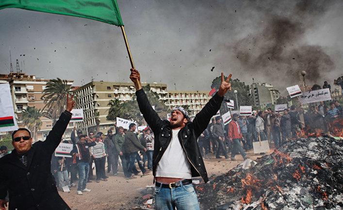 """Жители Бенгази сжигают портреты Муамара Каддафи, плакаты с его цитатами и """"Зеленую книгу"""" Каддафи."""