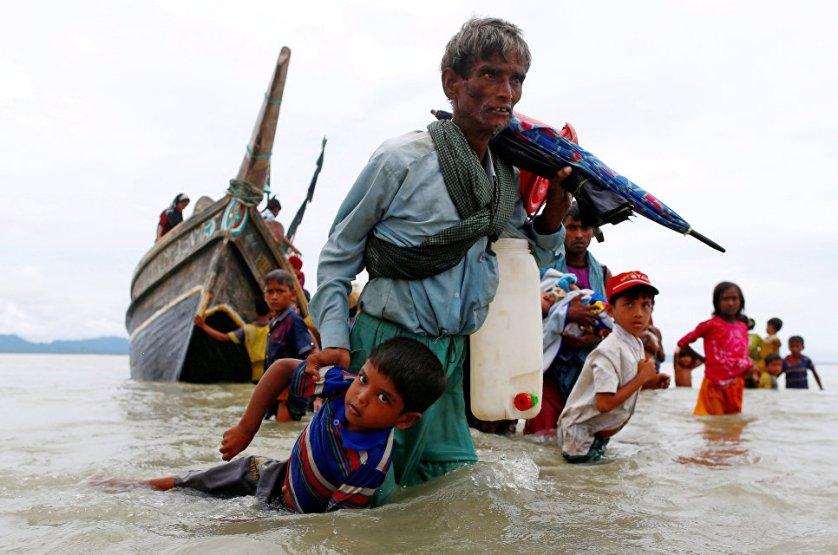 Мужчина из народности рохинджа вытаскивает ребенка из воды после пересечения границы Бангладеш через Бенгальский залив.