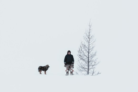a nenets man and his dog stand beside a tree in Siberia