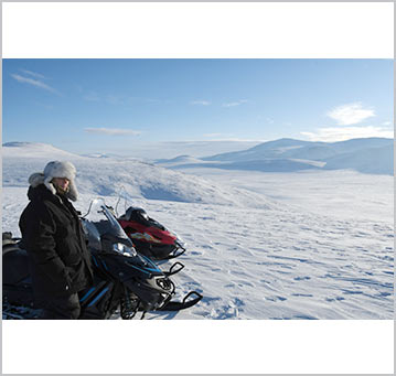 Tina Uebel stands next to her snowmobile overlooking the Arctic scenery