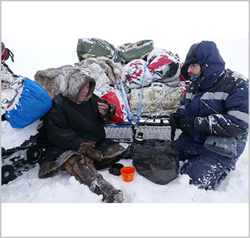 Tony and Vadimir shelter from the elements behind the snowmobiles and sledge