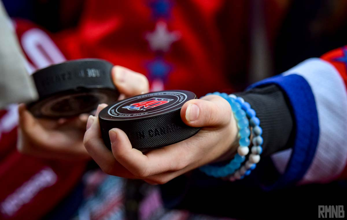 A fan holds out pucks to be signed