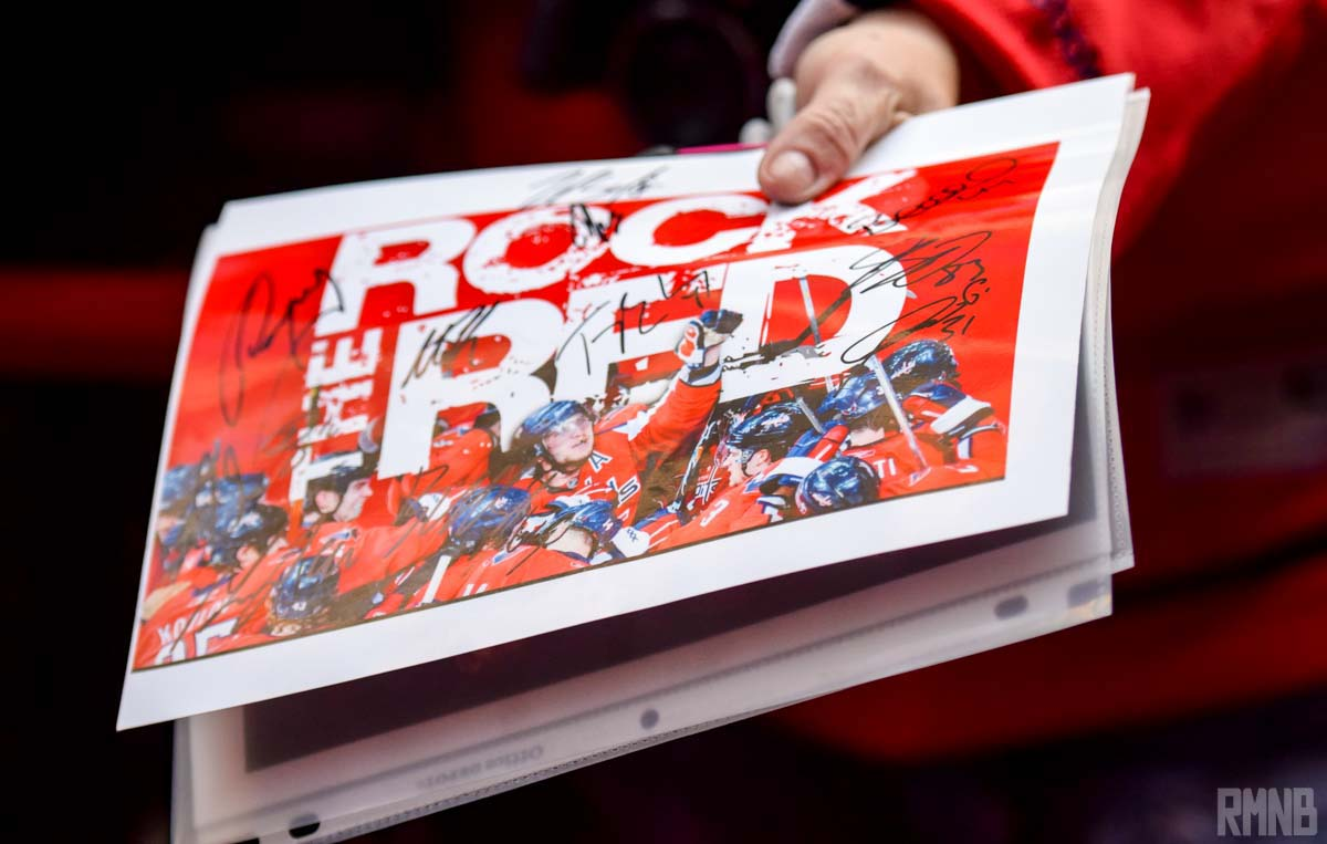 A fan holds a signed Rock The Red photo