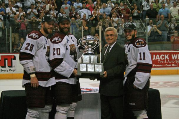 Alternate Captain Boyd Kane, Captain Bryan Helmer, AHL President David Andrews and Alternate Captain Keith Aucoin pose with the 2010 Calder Cup.