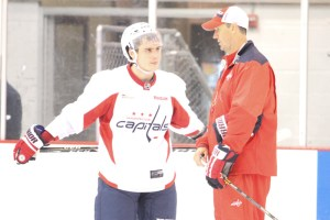 Capitals associate coach speaks to Dmitry Orlov on the ice after training camo practice on Wednesday.