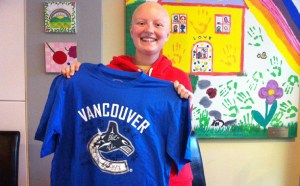 Brooke Malakoff holds up a signed Canucks shirt in 2012. (Photo: Vancouver Canucks)