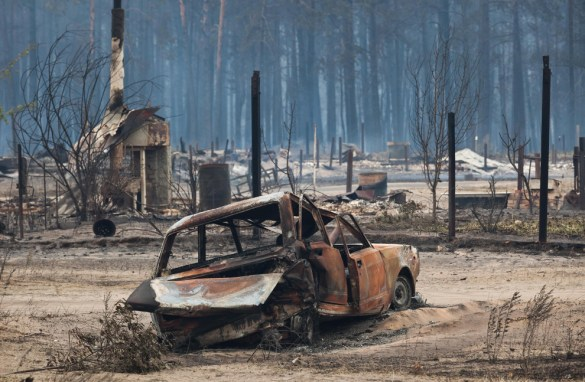 A charred car rests in front of a chimney - all that remains of a house that was burned to the ground. (AP Photo/Dmitry Chistoprudov)