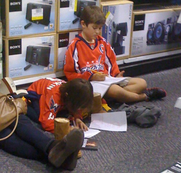 Kids do homework in line while waiting for Ovechkin to arrive.