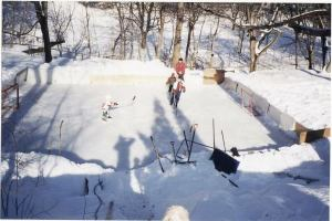 Peter, Tom, and James play hockey with their dad on their backyard rink.