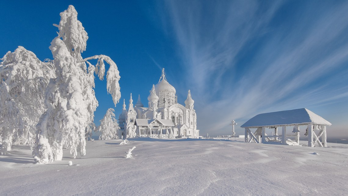 A snow covered field with a castle, tree and hut completely covered in snow (Winter Destination)