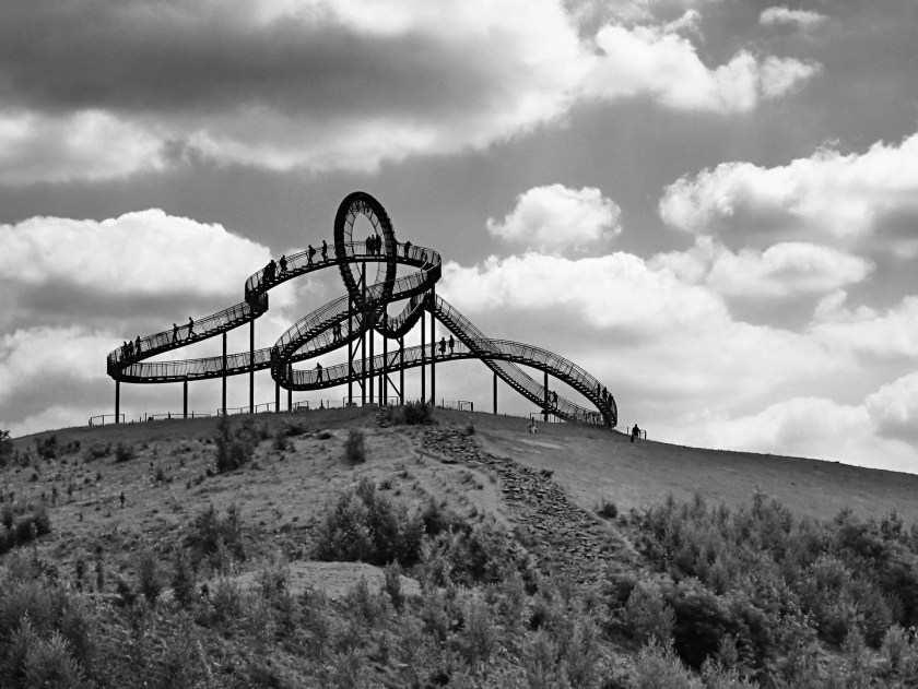 Roller coaster with loop in the distance, on hill