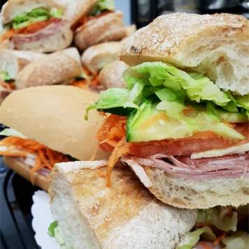 A pile of fresh baguettes with ham, salad and cheese looking really tasty!