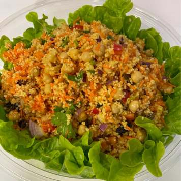 A bowl of coulourful couscous salad with chickpeas, grated carrot and red onion on a bed of lettuce.