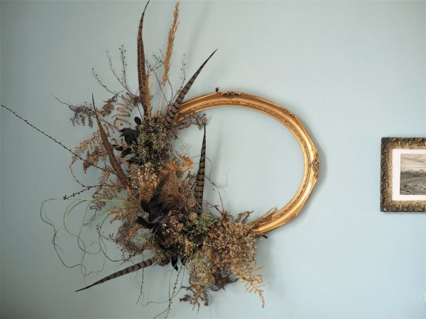 ornate frame with dried flowers and feathers