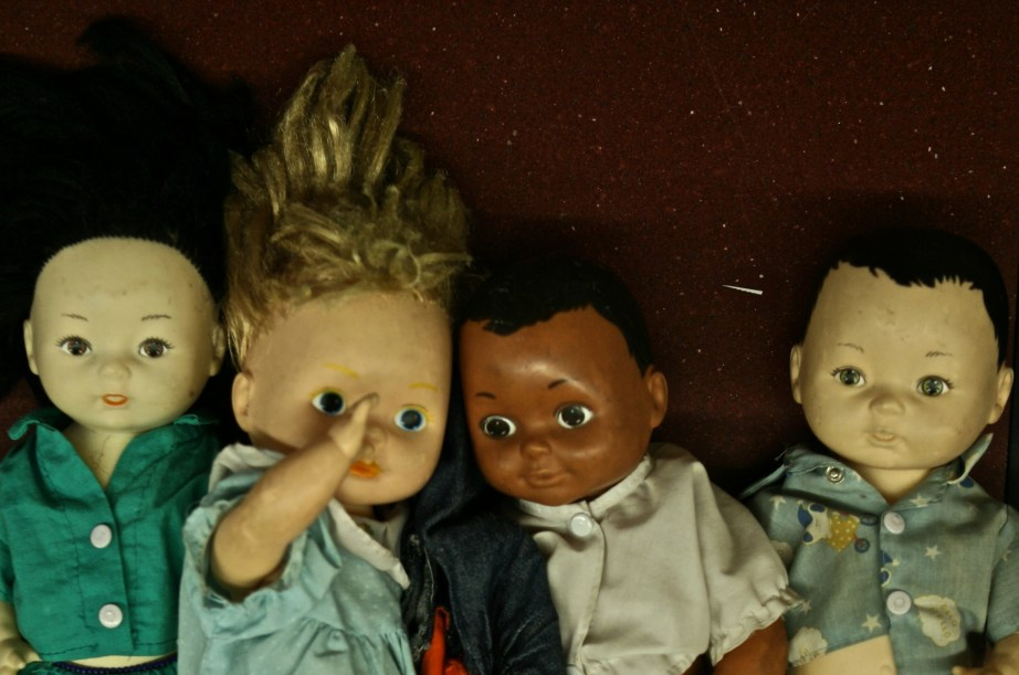 Four old school dolls, discarded from someone's classroom. Staring at me.