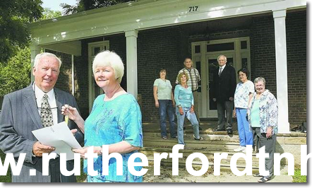 Cheryl Sommardahl, right, daughter of C.B. Arnette, hands the keys to the Ransom School over to Greg Tucker. In the background, standing on the porch of the house located at 717 N. Academy in Murfreesboro are the Rutherford County Historic Society board members, Vicki Norton, Shirley Farris Jones, Ernie Johns, Dr. E.C. Tolbert, Neil Blankenship and Susan Daniel. (Jim Davis/DNJ)
