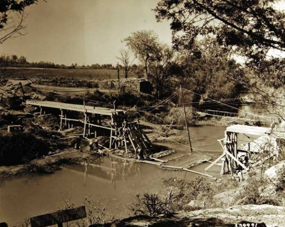 At the Stones River near Lascassas men work to repair a bridge that was damaged during the maneuvers. On Oct. 7, 1942, the community held a potluck dinner at the schoolhouse for the group of engineers that helmed the project.