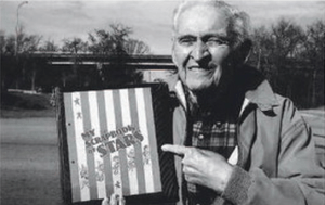 "Jere Warner holds his 80-year-old ""Scrapbook of Stars"" across from the now vacant site of the Consumers Ice Cream Co."