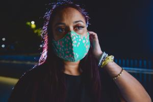 woman wearing Green curved face mask with Pink tile accents