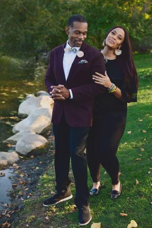woman walking with smiling man. man wears half tan/have black botanical print skinny bow tie