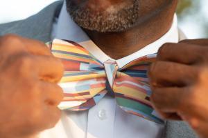 man adjusting multi color stripe bow tie