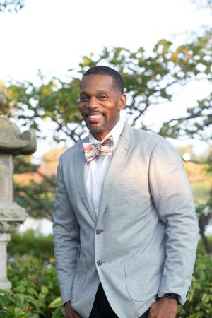 Smiling man wearing multi color stripe bow tie and grey blazer