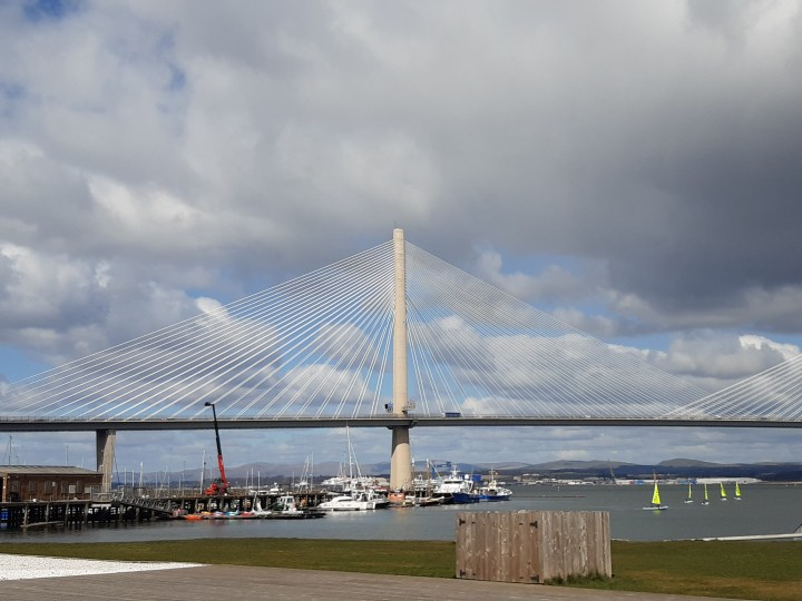 Queensferry Crossing, bridge above Port Edgar Harbour. Cable Bridge looking like sails against bright blue but clouded sky. Lawn and a huge wooden box in the foreground. Sailing boats