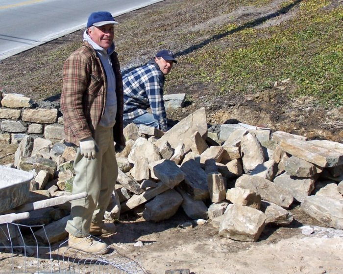 Primo Doria and Jose construct serpentine wall at Rider House of stones from GBMC's razed Bowen House.