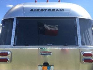 Texas Flag framed in the back window of an Airstream Travel Trailer.