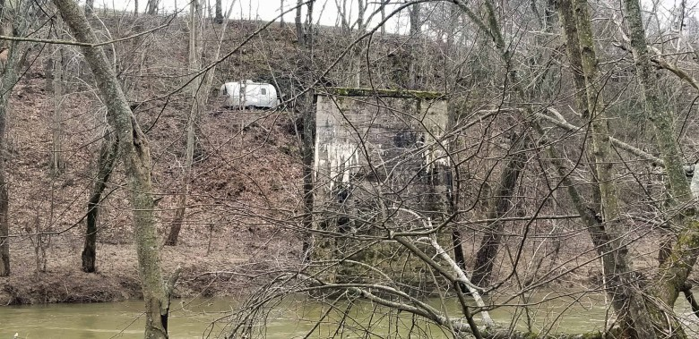 An Airstream travel trailer provides a recreational camp above the old railroad bridge.