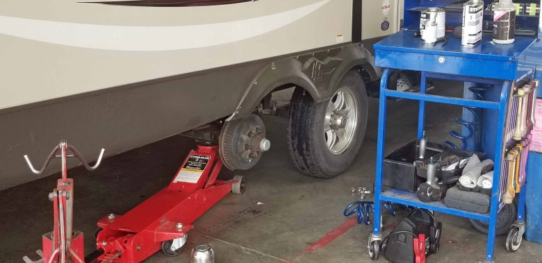 RV on hoist with tire removed