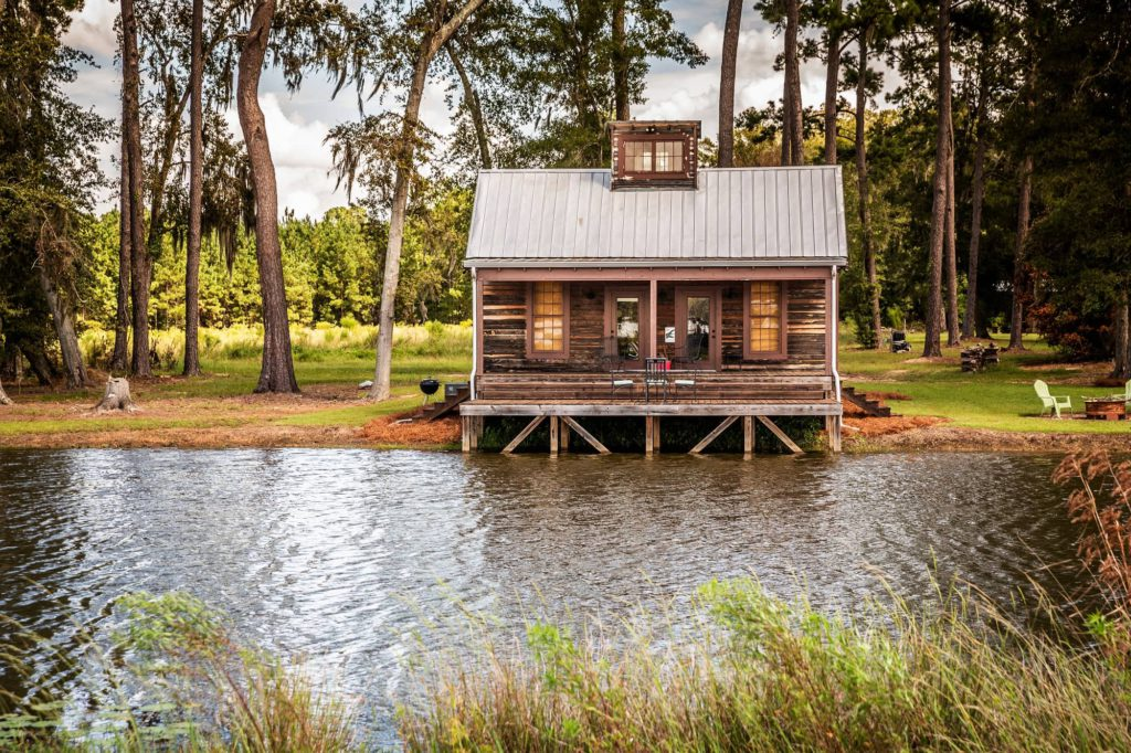 Scenic view of the exterior of a rural rustic wooden camp house used for fishing and hunting. The house is located on a large pond 2000cm