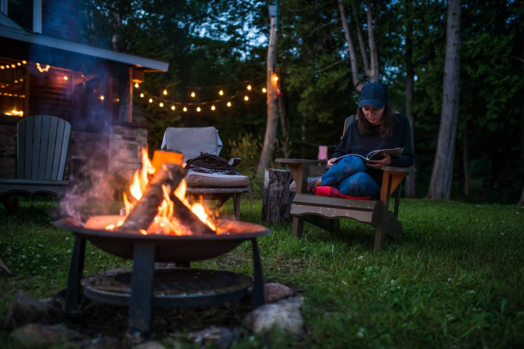 Young woman is reading a book by the campfire late evening at a beautiful canadian chalet 2000-cm