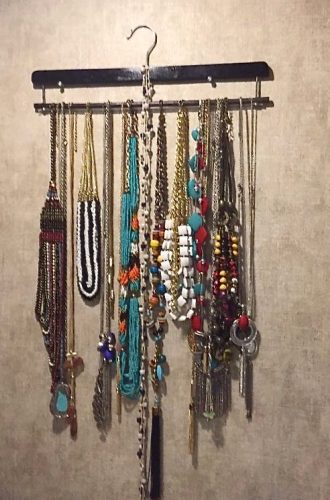 Necklaces hung on the wall using a tie rack
