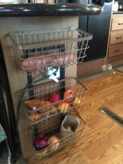 Baskets hung with mug hooks in kitchen for vegetable or fruit storage | rvinspiration.com | Ideas for your #camper, #motorhome, or #traveltrailer