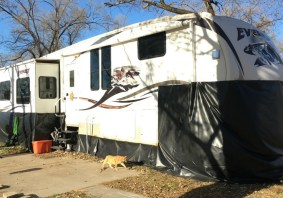 How We Made DIY RV Skirting from Billboard Vinyl hung with grommets and adhesive hooks for around $200