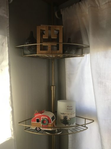 Flameless LED candle and vintage camper ornament on corner tension shower caddy as living room shelf