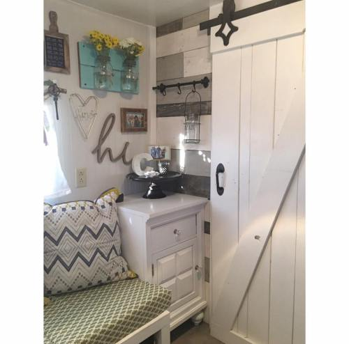 Wood plank wall and sliding barn door in toy hauler RV converted to Farmhouse style tiny home by Robyn Crowhurst