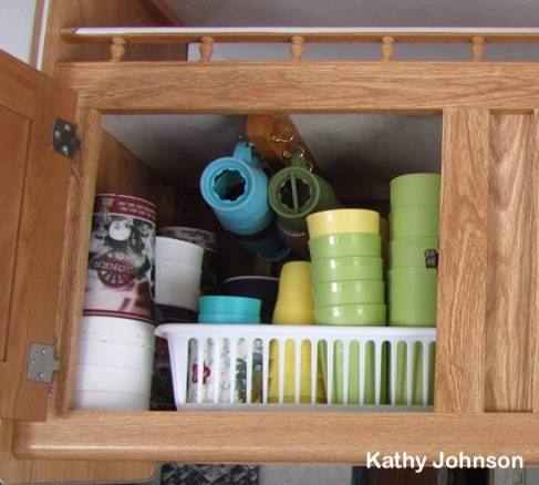 Mugs hung from hooks in top of #RV #kitchen cabinet
