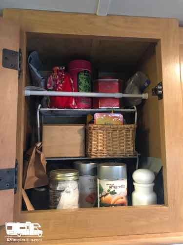 A tension rod can help keep things in an #RV #kitchen cabinet in place during travel.