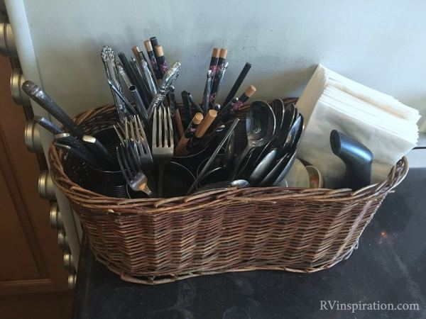 Basket with tin cans used as silverware storage in an RV kitchen