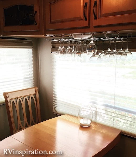 Wine glasses hung from bottom of RV kitchen cabinet